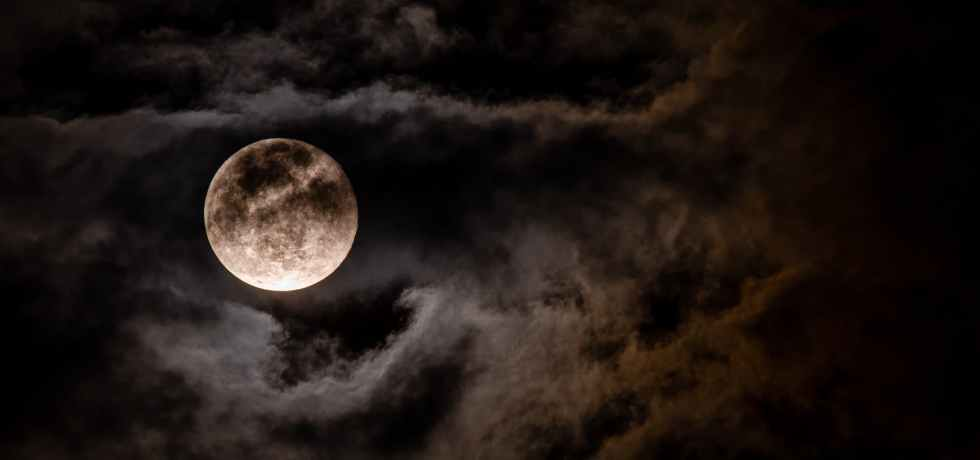 A spooky view of the moon behind moonlit clouds.