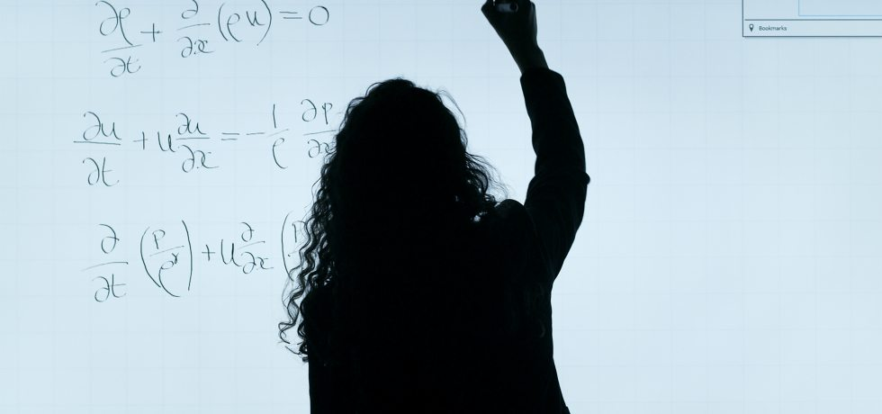A woman writing differential equations on the board in a math class.